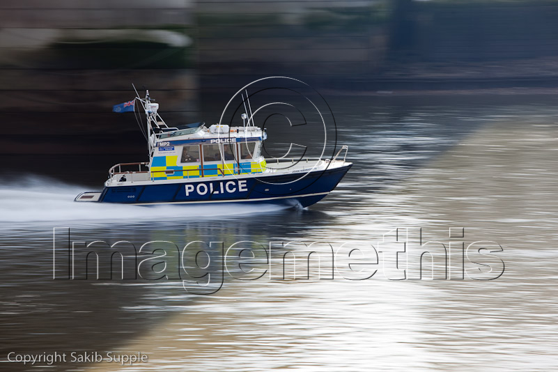 Police boat on the thames speeding along near blackfriars bridge